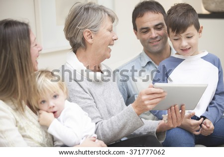 Happy family playing with tablet - stock photo