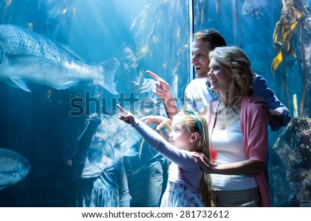 Happy family pointing a fish in the tank at the aquarium - stock photo