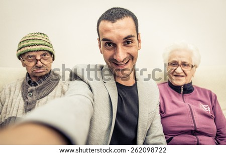 happy family portrait. grandson taking selfie with grandparents. concept about fun, family,aging,old people,seniority, technology,selfie and lifestyle - stock photo