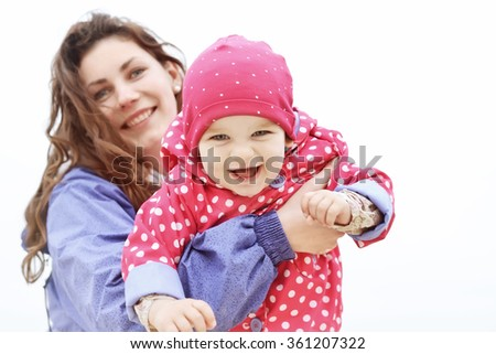 Happy family portrait. Laughing faces, mother holding adorable child baby girl smiling and hugging. Mom and daughter outdoors spring day. Beauty of smile, healthy kid, joyful, expressing love emotions