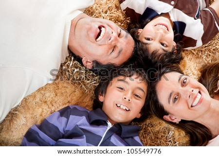 Happy family portrait laying on the carpet at home - stock photo