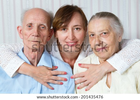 Happy family. Portrait of elderly parents and adult daughter happily looking at the camera. Senior man, woman with their caregiver at home. Concept of health care for elderly old people, disabled.  - stock photo
