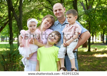 happy family portrait on outdoor, group of five people posing in city park, summer season, child and parent - stock photo