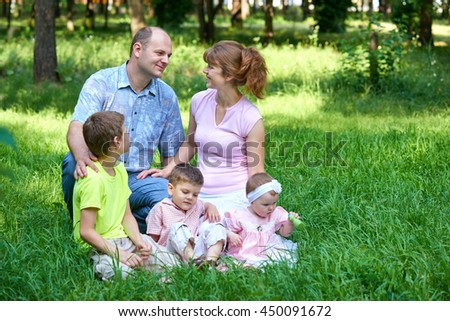 happy family portrait on outdoor, group of five people sit on grass in city park, summer season, child and parent