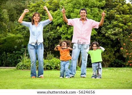 happy family portrait outdoors having fun jumping around - stock photo