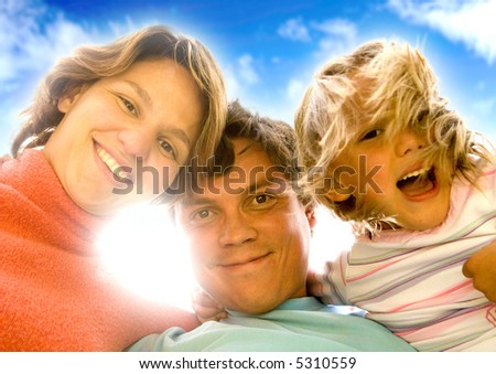 happy family portrait outdoors over a beautiful blue sky - sun flare behind the heads - stock photo