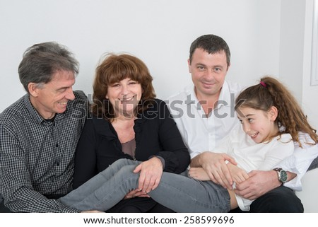 Happy family portrait with a loving elderly couple hugging their laughing young granddaughter