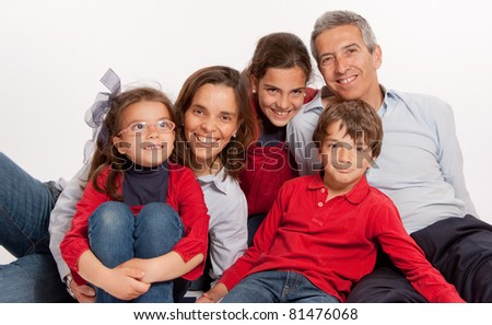 Happy Family portrait with all its members sitting on the floor - stock photo