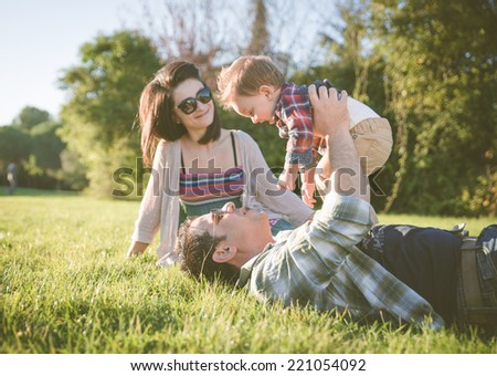happy family portrait. Young parents in a park with their one year old kid - stock photo