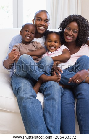 Happy family posing on the couch together at home in the living room - stock photo