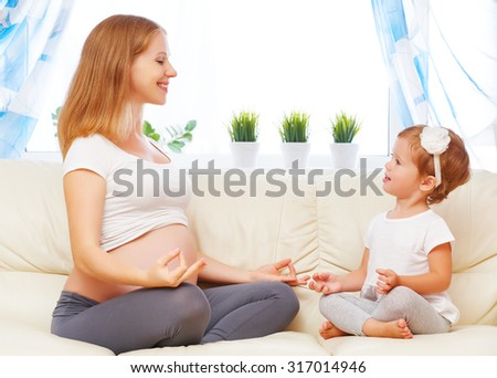 happy family. Pregnant mother and child daughterdo yoga, relax in the lotus position on sofa at home - stock photo