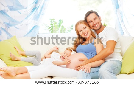 happy family. pregnant mother, father, and child daughter on sofa at home - stock photo