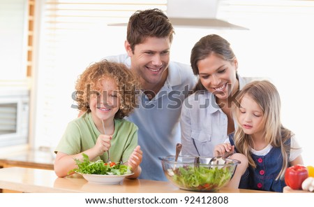 Happy family preparing a salad together in their kitchen - stock photo