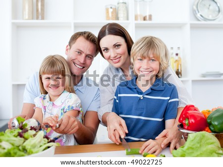 Happy family preparing dinner together in the kitchen - stock photo