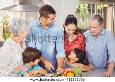 Happy family preparing food in kitchen at home - stock photo