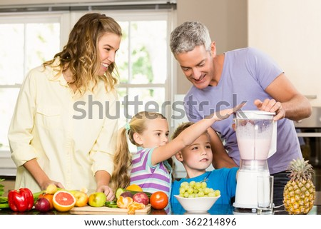 Happy family preparing healthy smoothie in the kitchen