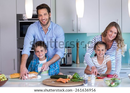 Happy family preparing vegetables together at home in the kitchen - stock photo