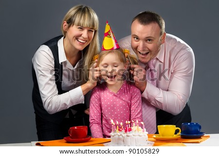 Happy family pulling on their daughter's ears in her birthday - stock photo