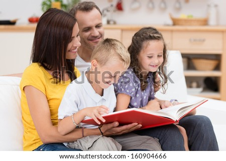Happy family reading a book together with attractive young parents grouped with their two small children on a couch in the living room