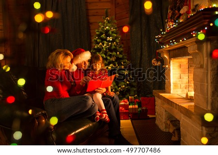 Happy family reading book at home by fireplace in warm and cozy living room on winter day