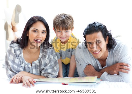 Happy family reading book together lying on the floor - stock photo