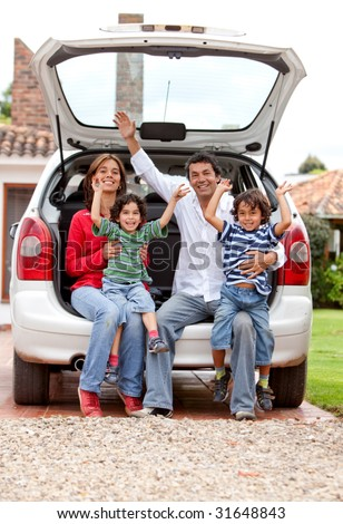 Happy family ready to go for a ride on their car - stock photo