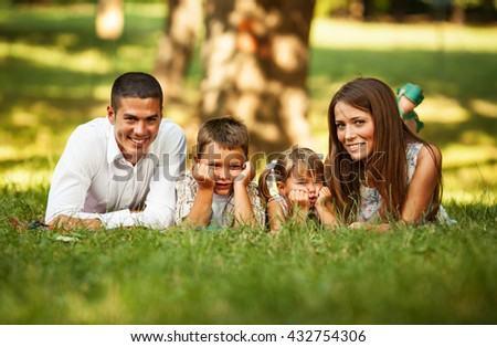 Happy family relaxing at the park on beautiful summer day - stock photo