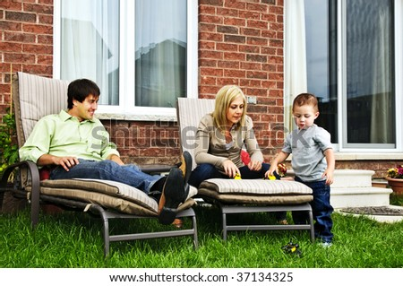 Happy family relaxing in backyard of new home with toddler - stock photo