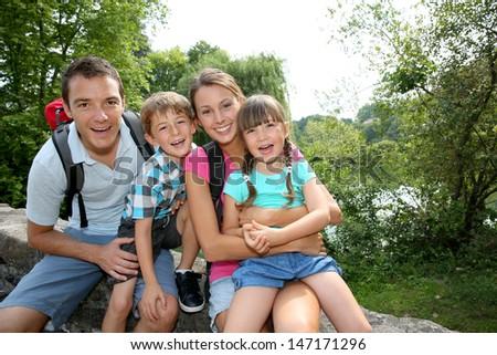 Happy family relaxing on a bridge  - stock photo