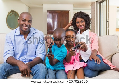 Happy family relaxing on the couch playing video games at home in the living room - stock photo