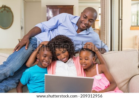 Happy family relaxing on the couch using laptop at home in the living room - stock photo