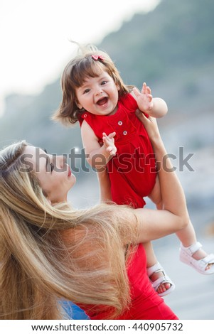 Happy family resting be sea in summer. Little girl and her mother playing on the beach. mother with her daughter playing - stock photo