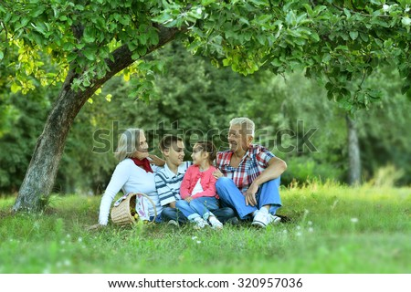 Happy Family resting in a summer park with apples - stock photo
