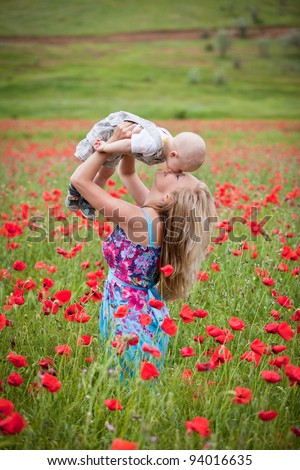 Happy family resting in the field with poppies - stock photo