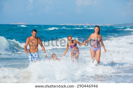 Happy family running by the sea with wave