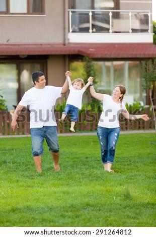 Happy family running on grass. - stock photo