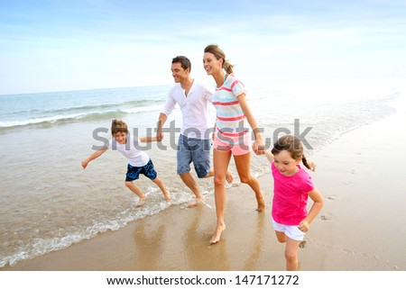 Happy family running on the beach - stock photo