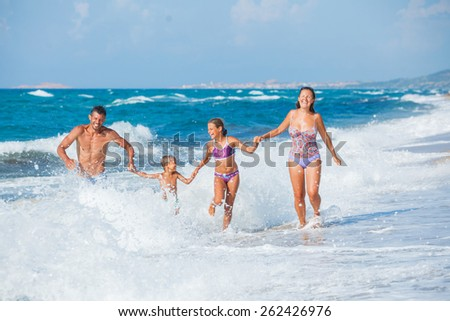 Happy family running on the sea with wave - stock photo