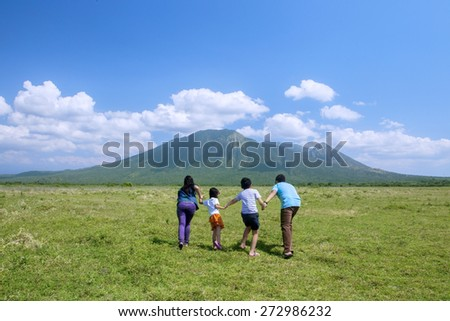 Happy family running to the mountain while holding hands - stock photo