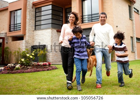 Happy family running together in the backgyard - stock photo