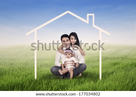 Happy family seated on the grass field and surrounded by home drawing - stock photo