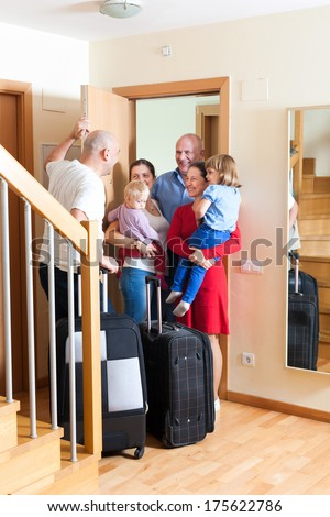 Happy family seeing off the relatives to home - stock photo