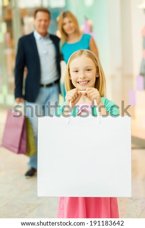 Happy family shopping. Cheerful family shopping in shopping mall while little girl showing her shopping bags and smiling - stock photo