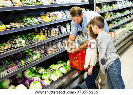 Happy family shopping vegetables at the grocery store - stock photo