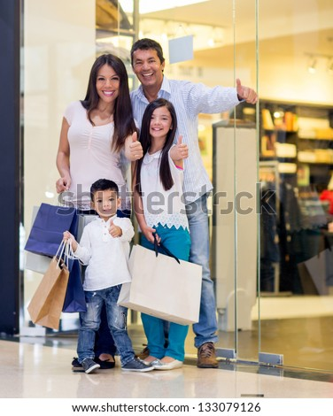 Happy family shopping with thumbs up and smiling - stock photo