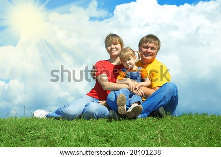 happy family sit on green grass under sky with clouds - stock photo