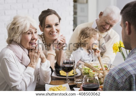 Happy family sitting beside table during dinner, granddaughter sitting on grandfather's lap - stock photo