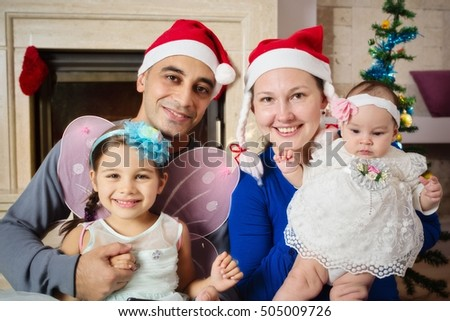 Happy Family Sitting By Fireplace and Christmas Tree