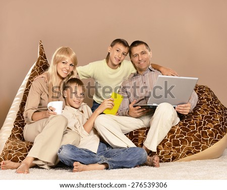Happy family sitting in a chair with a laptop