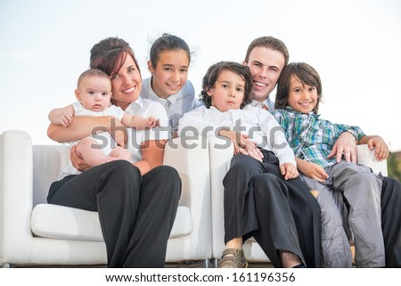 Happy family sitting in armchairs outside
